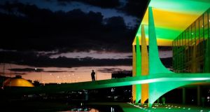 A security guard walks in front of the Planalto Palace In Brasilia as it is lit up in the colours of the Brazilian national flag ahead of the World Cup. Photograph: Ueslei Marcelino/Reuters