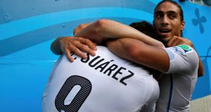 Uruguay's Luis Suarez (L) and Martin Silva (R) hug their teammate Diego Godin (not visible) after he scored a goal against Italy during their 2014 World Cup Group D soccer match at the Dunas arena in Natal June 24, 2014.  REUTERS/Toru Hanai (BRAZIL - Tags: SOCCER SPORT WORLD CUP)