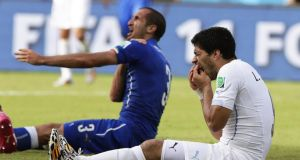 Italy's Giorgio Chiellini claims he was bitten by Uruguay's Luis Suarez as the striker holds his teeth at the Estadio Arena das Dunas in Natal. Photograph: EPA