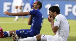Italy's Giorgio Chiellini  complains to the referee and claims he was bitten by Uruguay's Luis Suarez.