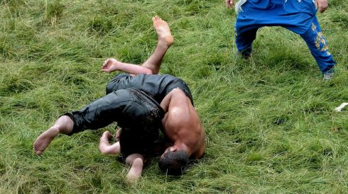 The struggle: A referee watches as two wrestlers grapple in the grass. Photograph: Erden Sahin/EPA