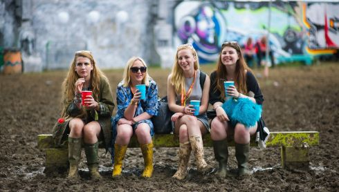 Four festival goers find a bench to sit down and have a drink. Photograph: Matt Crossick/PA Wire