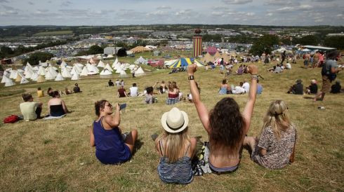 Festival goers enjoying the hot weather from a good vantage point at the Glastonbury site.  Photograph: Yui Mok/PA Wire