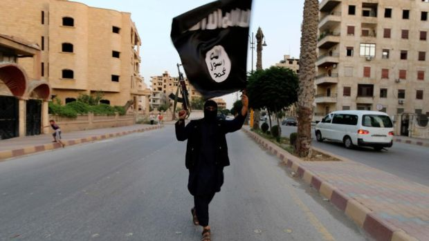 A member loyal to Isis waves a flag of allegiance to the militant group, in Raqqa. Photograph: Reuters