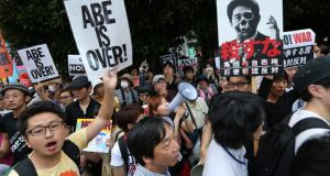 Protesters hold placards and shout anti-government slogans during a rally against Japanese prime minister Shinzo Abe's collective self-defence policy in Tokyo on Tuesday. Photograph: Christopher Jue/EPA