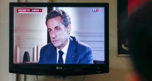 Local members and elected officials of the conservative UMP political party watch a taped television and radio interview on the TF1 evening news broadcast of former French President Nicolas Sarkozy.