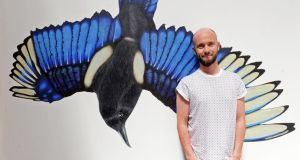 Colourful dichotomy: Niall Harbison. Behind him is artwork by Gearoid O'Dea. Photograph: Eric Luke