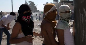 Masked young Palestinians during clashes  with Israeli police in the East Jerusalem area of Shuafat yesterday.  Photograph: EPA/Atef Safadi