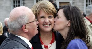 Joan Burton is embraced by  husband Pat Carroll and daughter Aoife at the opening of the 31st Dáil in Leinster House in 2011. Photograph : Matt Kavanagh
