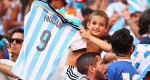An Argentina fan holds up a Gonzalo Higuain shirt during the quarter-finalagainst  Belgium at Estadio Nacional . Photograph:   Julian Finney/Getty Images