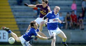 Wexford's Ciarán Lyng battles for possession with  Padraig McMahon and Peter O'Leary of Laois during Sunday's All-Ireland senior football qualifier at  Wexford Park, Wexford. Photograph: Inpho