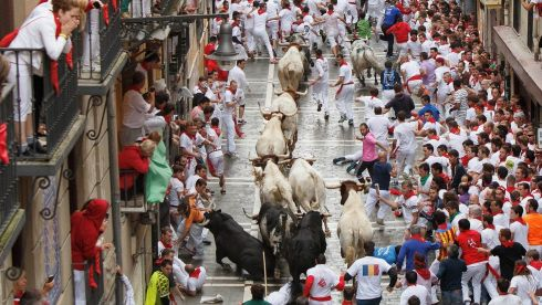 Crazy spectacle: People watch from balconies in Pamplona as bulls charge down the street below, slipping at times on the wet paving stones at people dive to get away. Photograph: Pablo Blazquez Dominguez/Getty Images