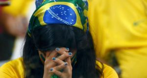A Brazil fan can't bear to watch during the rout at the hands of Germany in Belo Horizonte. Photograph: Eddie Keogh / Reuters