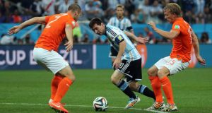 Lionel Messi of Argentina (centre) in action against Ron Vlaar of the Netherlands (left) and Dirk Kuyt   in Sao Paulo, Brazil. Photograph: Diego Azubel / EPA
