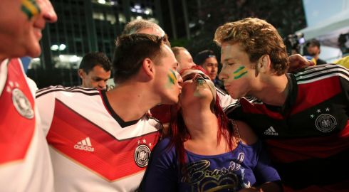 Fans of Germany kiss a Brazilian fan at the end of a broadcast of the game in Sao Paulo. Photograph: Nacho Doce/Reuters