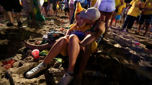 Brazil fans dejected on Copacabana Beach. Photograph: Pilar Olivares/Reuters