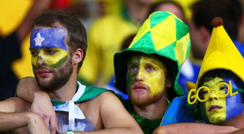 The Brazil fan on the left is quite red-eyed under the facepaint. A moment he'll want to forget - but probably never will. Photograph: Michael Steele/Getty Images