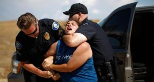A counter-demonstrator to protesters opposing arrivals of buses carrying undocumented migrants for processing at the Murrieta Border Patrol Station is arrested. Photograph: David McNew/Getty Images