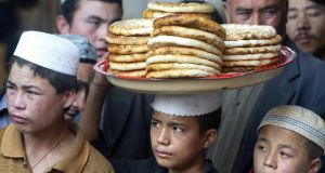 A Uygur boy carries a tray of  bread on his head. Ancient ethnic divisions resonate strongly in Xinjiang province, and more than 100 people have died in the past year in violence caused by growing tensions between the two biggest ethnic groups in the area, the Turkic-speaking Uighurs and the Han Chinese. Photograph: Frederic J Brown/AFP/Getty Images