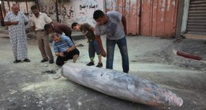 Palestinians look at the remains of a missile which witnesses said was fired by an Israeli aircraft on a street in Deir El-Balah in the central Gaza Strip. Photograph: Ashraf Amrah/Reuters