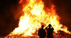 Members of the public take photographs at a bonfire on Sandy Row, Belfast last night. Photograph: Brian Lawless/PA Wire