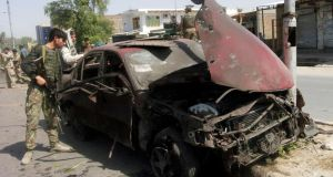 A member of the Afghan security force looks into a car which was destroyed  in a bomb attack in the eastern city of Jalalabad. Photograph: Parwiz/Reuters