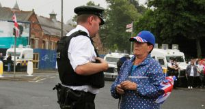 A loyalist supporter speaks to a Police officer as they await an Orange Order parade on Crumlin Road. Photograph: Brian Lawless/PA Wire