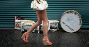 A female band supporter runs past a shopfront on her way to watch the start of the annual Twelfth march in Belfast. Photograph: Charles McQuillan/Getty Images