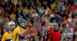 Clare's Brendan Bugler is shown a straight red card by referee Johnny Ryan during the All-Ireland SHC Qualifier Round 1 Replay at Wexford Park. Photograph: Donall Farmer/Inpho