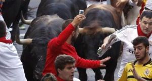 A Pamplona runner holds up his phone inches from the bulls. Photograph: Rafa Rivas/AFP/Getty Images