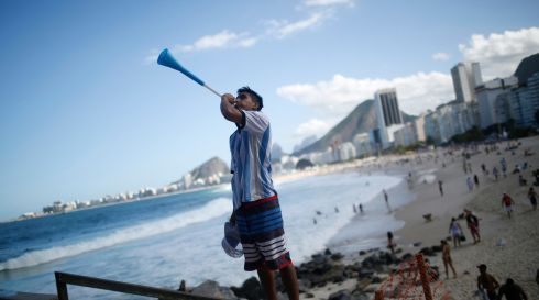 An Argentina fan blows into a vuvuzela on Copacabana beach prior to the World Cup final in Rio de Janeiro, Brazil.  Photograph: Dado Galdieri/Bloomberg