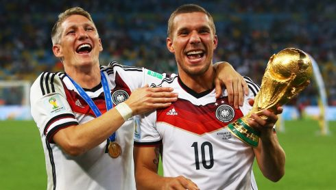 Bastian Schweinsteiger and Lukas Podolski of Germany celebrate with the World Cup trophy. Photograph: Julian Finney/Getty Images