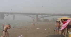 Bathers were  forced to run for cover as a hail storm blew up in Siberia. Screengrab: YouTube