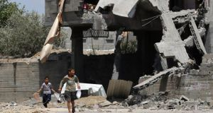 Palestinian boys walk past a destroyed house in the north of Beit Lahiya town in the northern Gaza Strip today. Photograph: Mohammed Saber/EPA