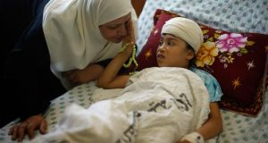 Nine-year-old Palestinian Maryam Al-Masri, whom hospital officials said was wounded in an Israeli air strike, listens to her grandmother as she lies on a bed while receiving treatment at a hospital in Gaza City yesterday. Photograph: Reuters/Mohammed Salem