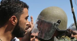 A Palestinian protester argues with an Israeli soldier during a protest against  air strikes in the Gaza Strip at a  checkpoint near Nablus yesterday. The aim of international mediators would be to forge a compromise package acceptable to both that would bring an end to the bloodshed quickly. Photograph: Abed Omar Qusini/Reuters
