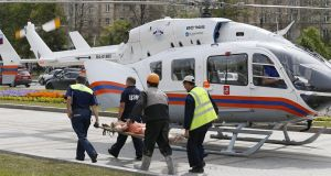 Rescuers carry an injured passanger to an ambulance helicopter from the 'Park Pobedy' metro station. Photograph: Yuri Kochetkov