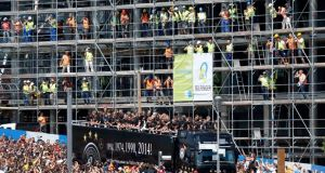 Construction workers take pictures as Germany's 2014 Brazil World Cup squad proceed in an open-top truck through Berlin during a parade to mark the team's victory over Argentina in Brazil. Photograph:   Morris Mac Matzen/Reuters