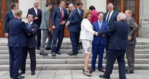 Taoiseach Enda Kenny  and Tanaiste Joan Burton  with new Ministers of State on the steps of Government Buildings yesterday. Photograph: Eric Luke / The Irish Times