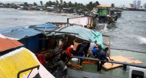 Filipino residents dismantle a shanty after it was damaged by a barged caused by strong winds and rain brought by typhoon Rammasun along the coastline of the Tondo slum area, in Manila. Photograph: Dennis M. Sabangan