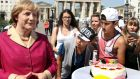 Tourists look at a wax figure of German chancellor Angela Merkel in front of the Brandenburg Gate in Berlin yesterday.  Madame Tussauds wax museum put the figure on public display to mark Ms Merkel's 60th birthday on Thursday. Photograph: Wolfgang Kumm/EPA