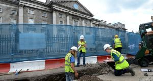 Archaeologists  examine a works site on the Luas cross-city route  outside Trinity College Dublin today after possibly medieval human remains were uncovered. Photograph; Dara Mac Dónaill/The Irish Times