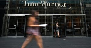 A woman walks past the Time Warner Center near Columbus Circle in Manhattan yesterday.  Rupert Murdoch's 21st Century Fox Inc said  it had offered to buy the company in  a move that would unite two of the world's most powerful media conglomerates, but Time Warner rebuffed its offer. Photograph:  Reuters