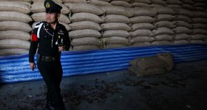 A soldier walks past sacks of rice at a warehouse in Ayutthaya province, north of Bangkok. The military is checking rice warehouses nationwide to work out how much grain was stockpiled by the government it ousted in May and check on rice quality amid alleged corruption during the time the policy was run by former prime minister Yingluck Shinawatra. Photograph: Chaiwat Subprasom/Reuters