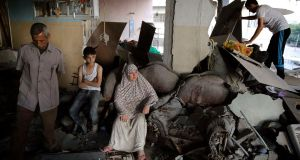 A Palestinian family gathers inside a damaged home, which police said was targeted in an Israeli air strike on Gaza City. Photograph: Finbarr O'Reilly/Reuters