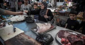 A Palestinian women buys from a butcher at a street market in Gaza City on Thursday. Daily life resumed for a short while during a five-hour  ceasefire between Israel and Gaza requested by the United Nations. Photograph: Oliver Weiken/EPA