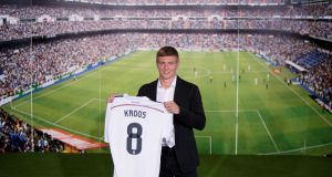 Toni Kroos  with his new Real Madrid shirt during his official unveiling at Santiago Bernabeu Stadium  in Madrid, Spain yesterday. Photo:  Pablo Blazquez Dominguez/Getty