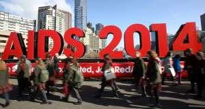 Members of the public walk past signage on the Princes Bridge for the 20th International AIDS Conference in Melbourne today. Photograph: Graham Denholm/Getty Images