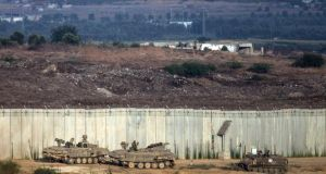 Israeli tanks sit at  the wall seperating Gaza and Israel  near Sderot this morning. Photograph:  Andrew Burton/Getty Images