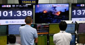Employees of a foreign exchange trading company look at monitor displaying a TV programme featuring the downed Malaysian Airlines MH17, as other monitors displaying the Nikkei share average  ,the exchange rates between the Japanese yen and the US dollar and euro. Photograph: Reuters